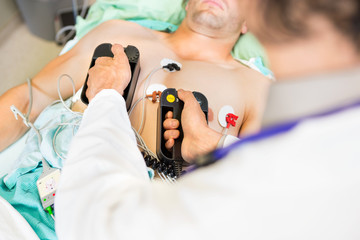 Doctor Defibrillating Male Patient In Hospital