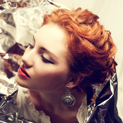Arty portrait of a fashionable queen-like red-haired woman