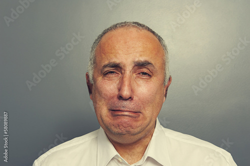 sorrowful senior man over grey background