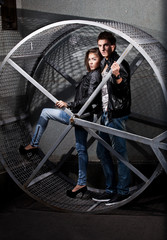 couple in leather coats posing in metal construction on street