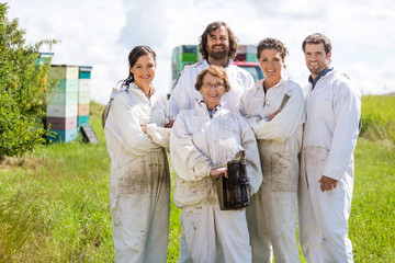 Team Of Confident Beekeepers At Apiary