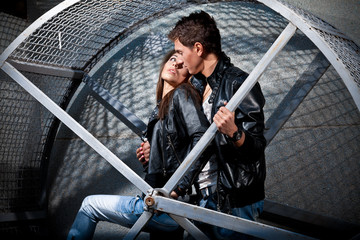 Young man and woman hugging on street in metal cage