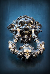 Antique knocker on a wooden door, Rome