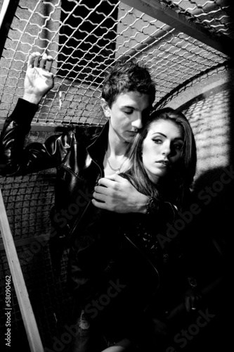 portrait of man hugging woman from back near metal fence