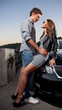 Handsome macho hugging sexy girl on hood of the car