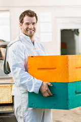 Happy Male Beekeeper Carrying Stack Of Honeycomb Crates