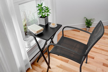 Chair and table in a room with green plants
