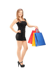 Young female in black dress holding shopping bags