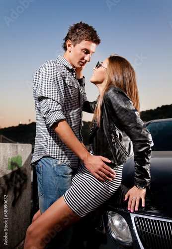 Beautiful young couple hugging on car hood