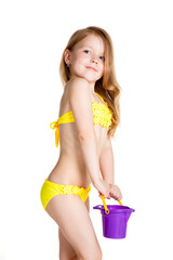 little blonde happy girl in yellow swimsuit holding toy purple b