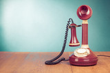 Old retro telephone on wood table front mint green background