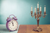 Retro clock and candle holder on table front mint green