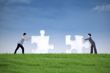 Business partner putting together two puzzle pieces