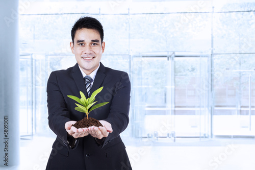 Smiling businessman holding a plant