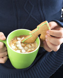 A closeup of a boy dipping a sugar cookie in hot chocolate with