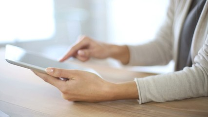 Closeup of woman's hand sliding on tablet screen