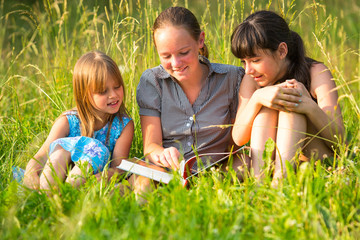 Three little sister reading book in natural environment