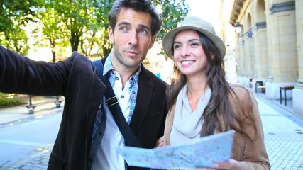 Couple of tourists walking in town with map