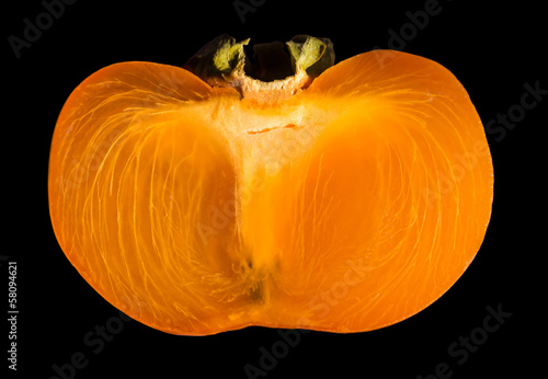 Slice of persimmon isolated on black.