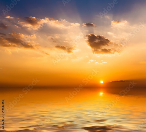 Beautiful sunset with clouds reflected in water.