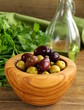 marinated green and black olives (Kalamata) in a wooden bowl