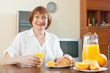 Positive mature woman having breakfast
