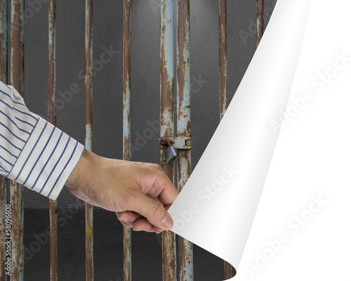 Man change locked iron bars door with dark space to white empty