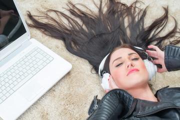 Rassige Frau mit Laptop hört Musik