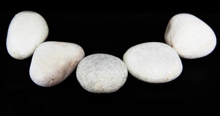 White zen stone over black background