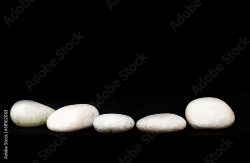 White zen stone over black background
