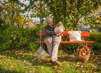 Seniorn macht eine Pause auf der Gartenbank