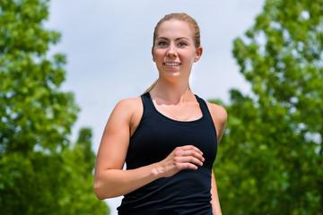 Sport und Fitness - Junge Frau joggt im Park