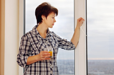 Awaiting woman stands by the window with a glass of juice