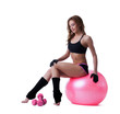 Smiling athletic woman sitting on fitness ball