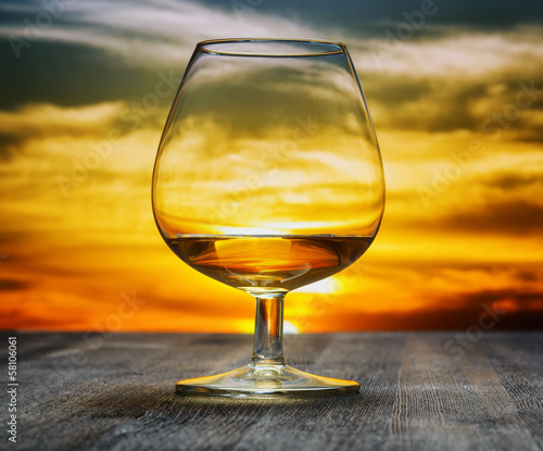 Glass of brandy on evening sky background
