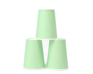 Arrangement of green recycling paper glasses on white background
