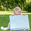 Baby sitting with laptop in a meadow