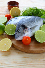 fresh fish on the board with lemons and limes