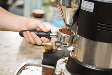 Barista Holding Portafilter With Ground Coffee In Cafe
