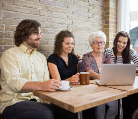 Woman With Friends Using Laptop At Cafe Table
