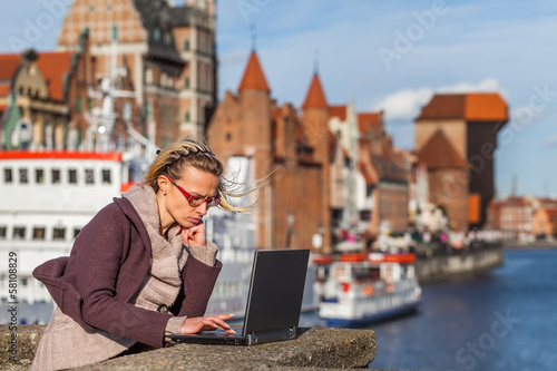 Woman with laptop on the bridge