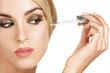 beautiful model applying a skin serum treatment