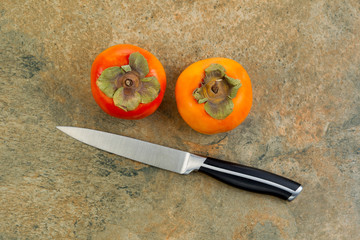Persimmons with Paring Knife on Natural Stone Counter Top