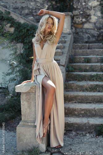 beautiful girl with blond hair in beige dress