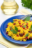 couscous with curry, dried cranberries and herbs, vertical