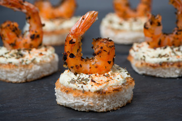 festive appetizer with spicy shrimps on toast, close-up
