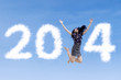 Businesswoman jumping with new year 2014