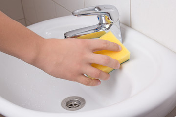 Male hand with sponge cleaning sink