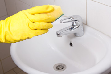 Hand in yellow glove with sponge in bathroom