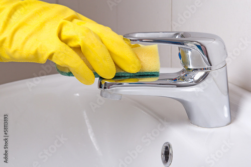 Hand in yellow glove with sponge cleaning sink